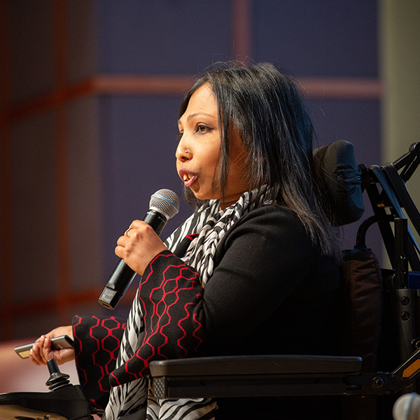 Neena Nizar, seated in a wheelchair, speaks to the audience at Rare Disease Day at NIH 2020 about her experience with the rare disease metaphyseal chondrodysplasia.
