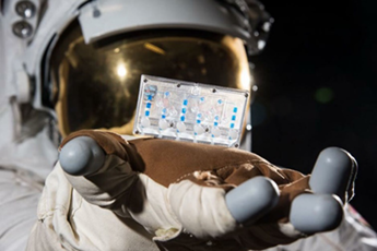 Photo of Astronaut with hand out showing a tissue chip hovering above hand.