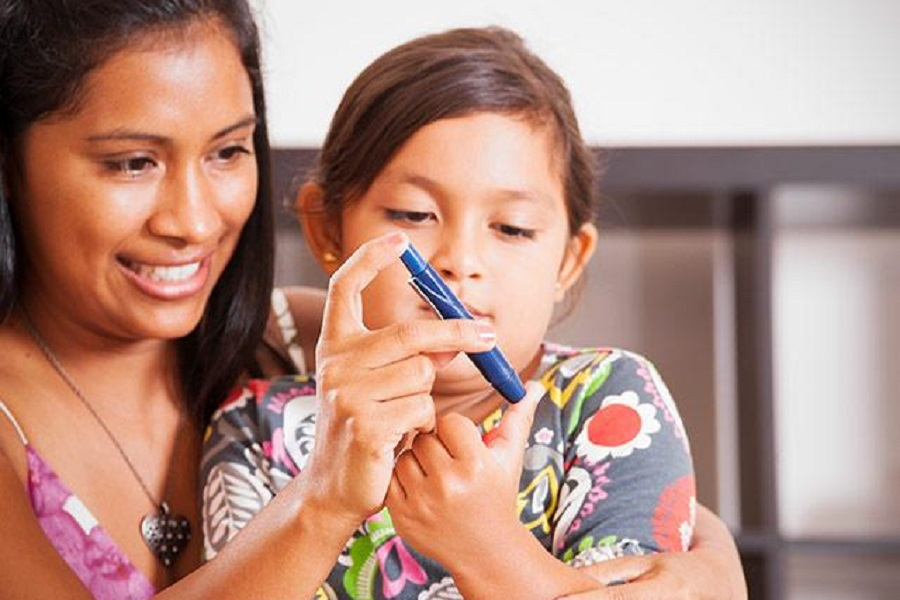A parent helps a child monitor her blood sugar level