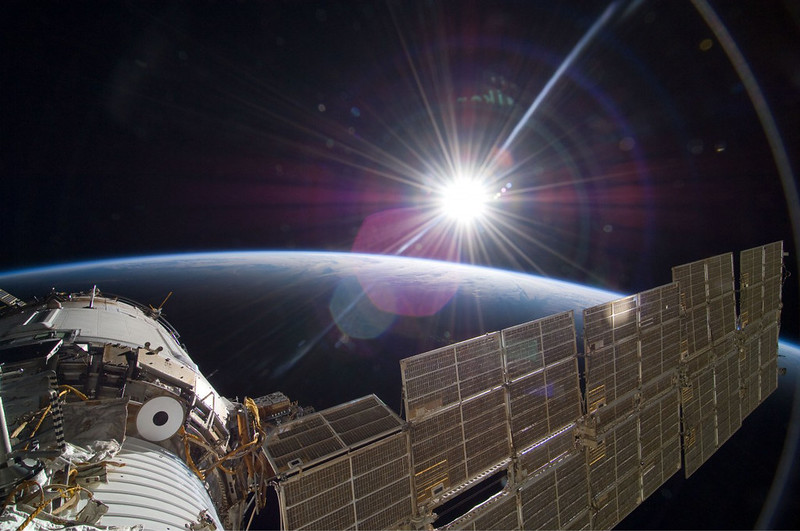 The sun rising over the International Space Station and Earth