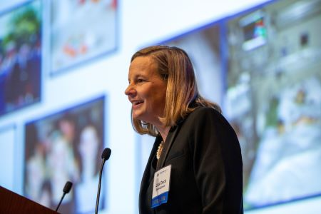 Lisa Deck speaks at lectern about her experience with a rare disease at Rare Disease Day at NIH 2020. Images related to her diagnostic journey are projected on a large screen behind her.