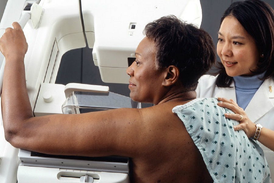 Doctor performing panoramic mammogram on a patient
