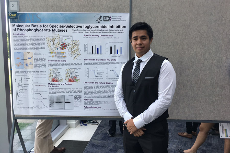 "Bryan Queme in front of a poster display titled ""Molecular Basis for Species-Selective Ipglycermide Inhibition of Phosphoglycerate Mutases"""