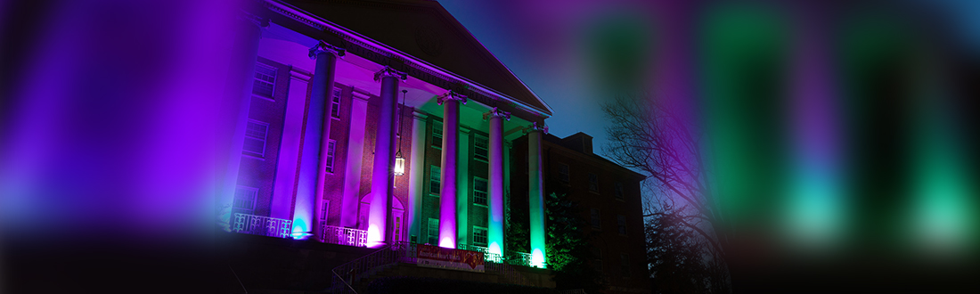 NIH Building 1 lit up at night with Rare Disease Day colors.