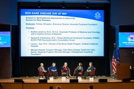 "The moderator and four panelists from the session ""Nontraditional Approaches to Improving Access for Rare Diseases"" talk in front of a large slide projection at Rare Disease Day at NIH 2020."
