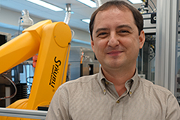 Anton Simeonov, Ph.D., and a high-throughput screening robot.
