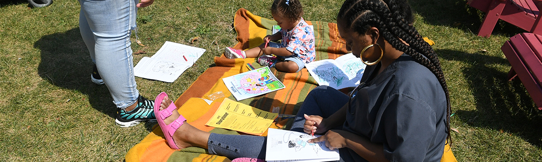 "A family sits on a blanket coloring pages from the ""Sofia Learns About Research"" activity book."