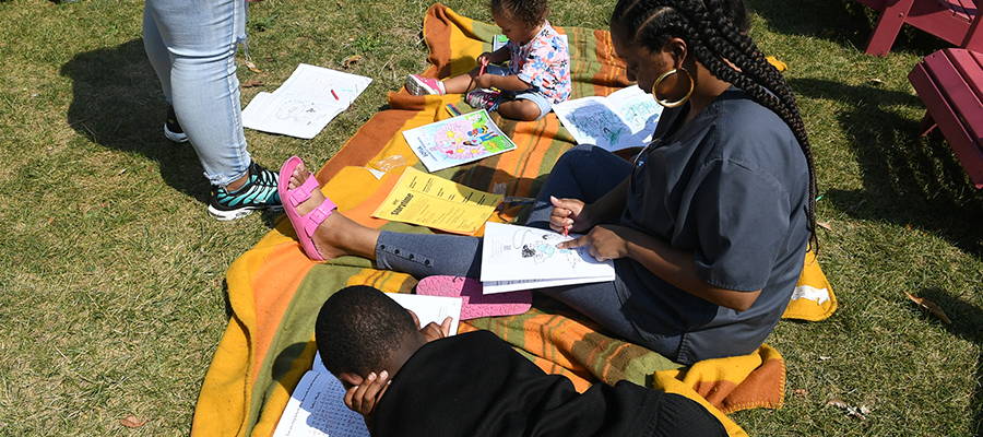 """A family sits on a blanket coloring pages from the """"Sofia Learns About Research"""" activity book."""