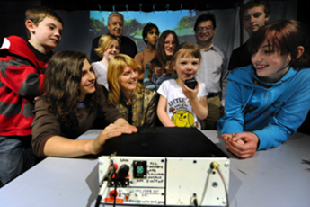 Photo of group of adults and kids smiling as little girl uses a device to talk to astronaut.