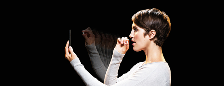 A woman holds a pill up to a smartphone and prepares to take the pill.