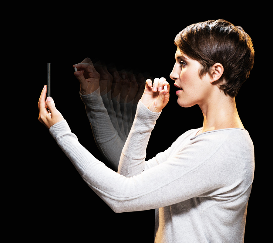 A woman holds a pill up to a smartphone and prepares to take the pill