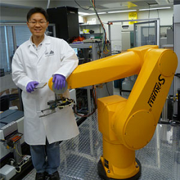 NCATS researcher Sung-Wook Jang stands next to the high-throughput screening robotic system used to identify potential treatments for Charcot-Marie-Tooth disease.