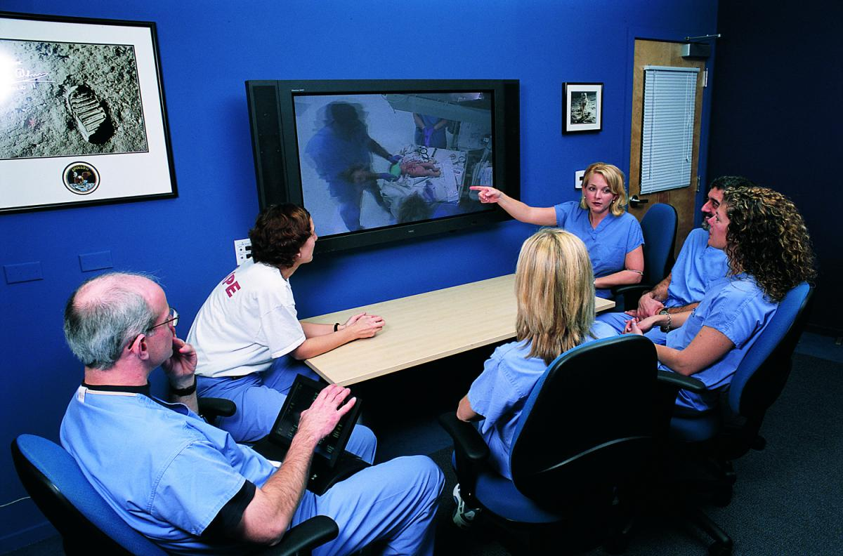 Group of scientists around a tv/computer screen