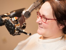 Study volunteer Jan Scheuermann, who has quadriplegia, guides food into her mouth with a thought-controlled robot arm thanks to the help of a multidisciplinary research team. (University of Pittsburgh Medical Center Photo)