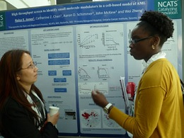 NCATS Post-Baccalaureate Intramural Research Training Award fellow Raisa Jones (right) discusses a high-throughput screen for Acute Myeloid Leukemia with an NIH Research Festival participant. (NCATS Photo/Geoff Spencer)