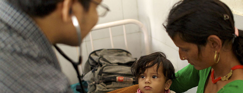 Doctor examining small child being held by her mother.