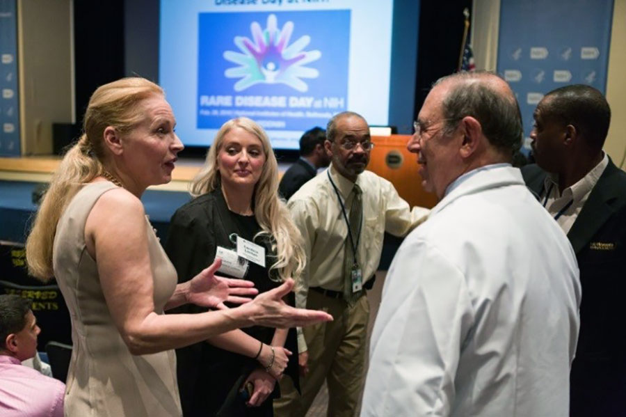 Patricia Weltin and John Gallin speak to each other at the 2016 Rare Disease Day at NIH