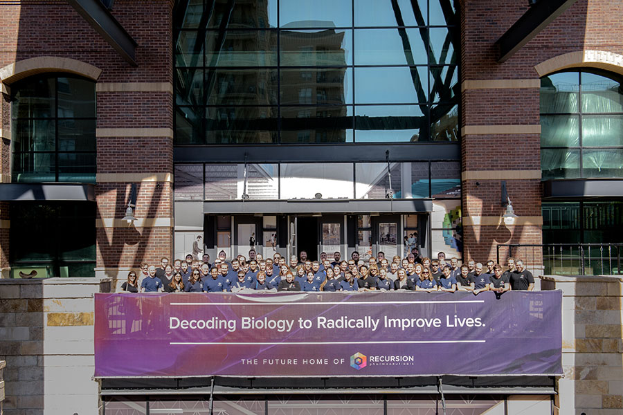 "The Recursion team poses outside its new headquarters with a banner reading ""Decoding Biology to Radically Improve Lives."""