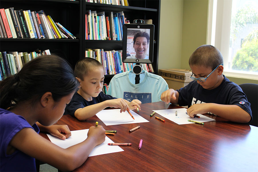 Students sit around a table doing classwork. Noah attends the session using a robot.