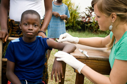 Medical aid worker delivers a vaccine to a small boy.