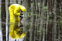 Researcher in hazmat gear examines water samples